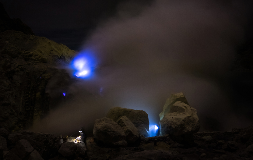 Kawah Ijen's crater emitting electric blue flames as a result of sulfurous gases in contact with oxygen.