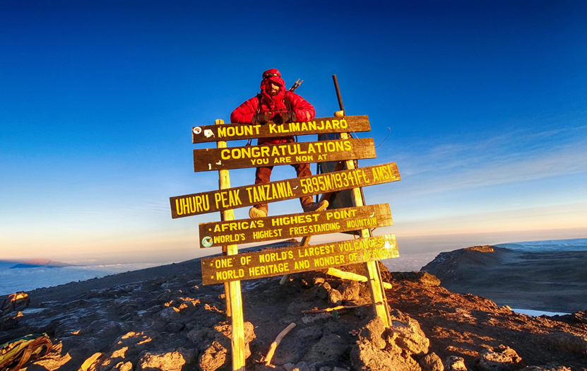 Hiker poses hanging on the sign that marks the arrival at the top of Mount Kilimanjaro to celebrate the end of the climb.