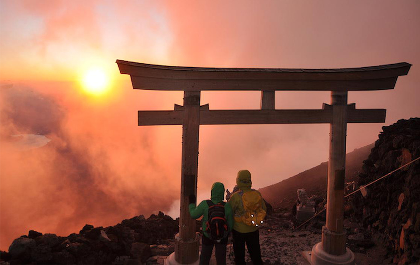 Two hikers observing a spectacular red & foggy sunrise under a torii gate at the top of Mount Fuji.