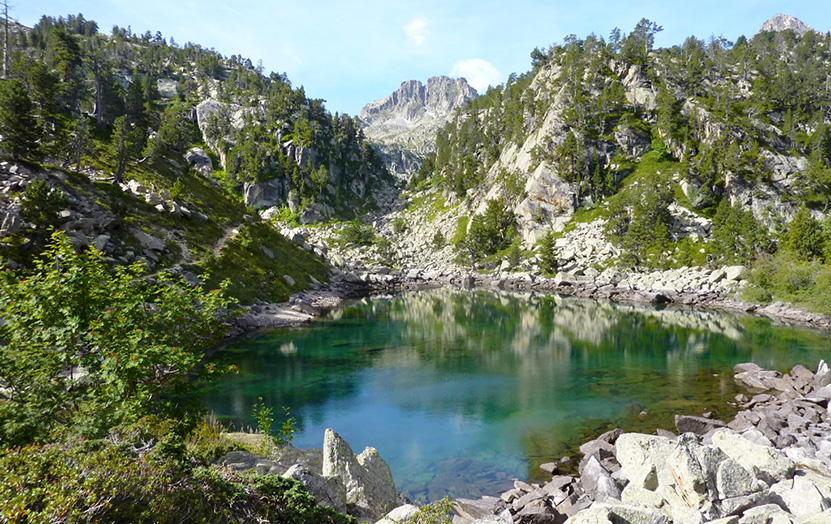 Estany de Gerber with its crystal clear waters and Bassiero Peak in the background.