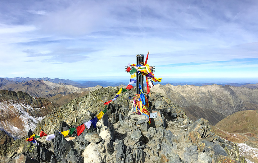 Summit of La Pica d'Estats where a cross stands fully covered with colored flags.