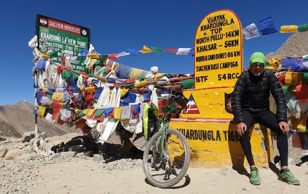 """Mikel Bringas and his bicycle on the mountain pass of """"Khardung La"""" in India."""