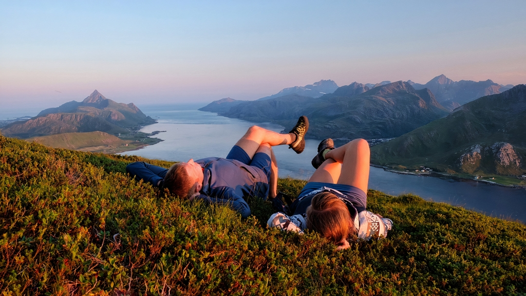 Two people soaking up the last rays of the sun along a hiking trail in Offersøya, Norway