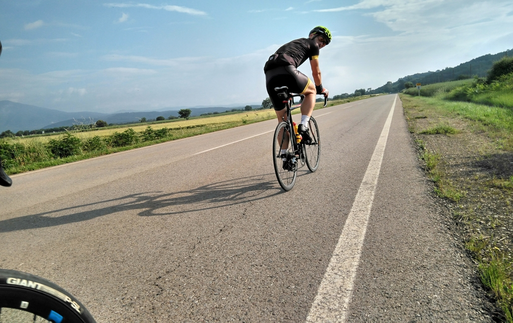 A cyclist on a paved road, pedaling on their road bike