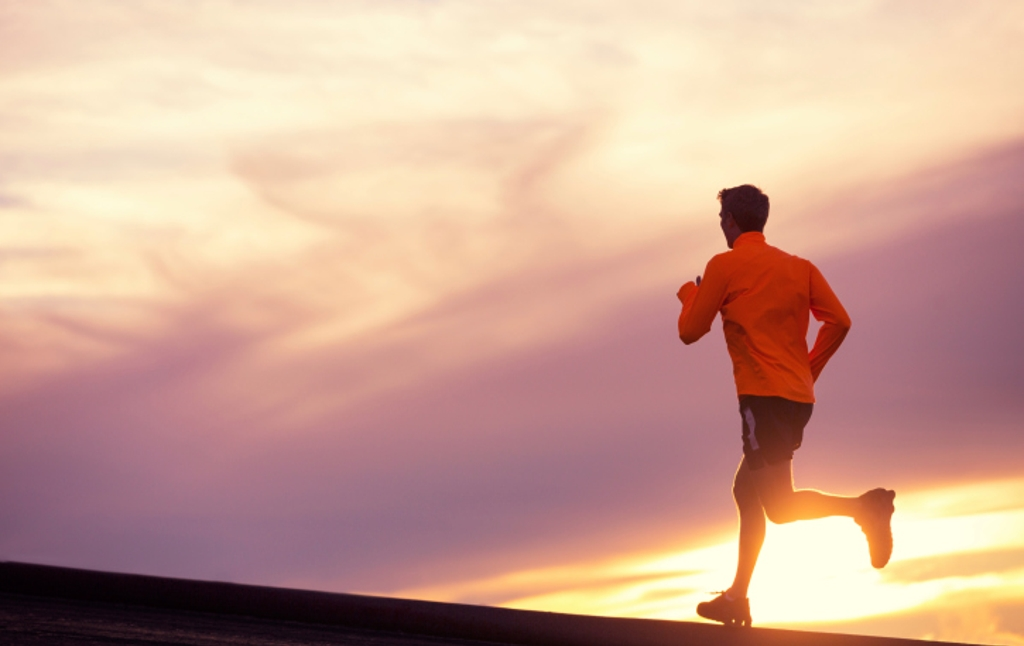 A runner on a running outing during a reddish sunset.