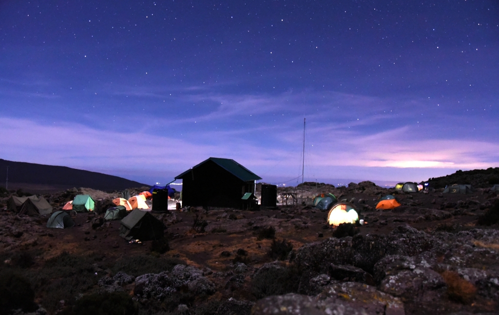 Tents camping under a starry sky on one of the paths along the Lemosho and Shira routes, in the Kilimanjaro National Park.