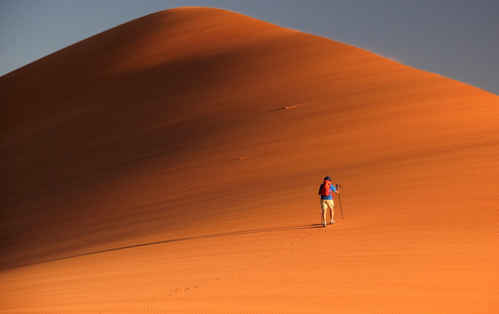 A hiker walking along the dunes at Tin Merzouga with a backpack and hiking poles.