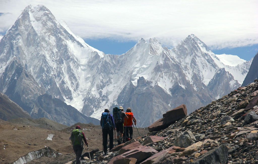 A group of hikers trekking on the Baltoro Glacier, with snow-capped mountains as an impressive backdrop.