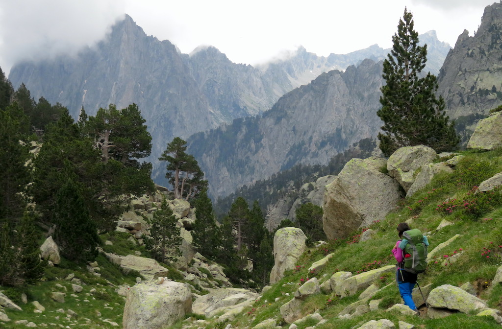 A hiker walking with a trekking backpack along the Carros de Foc trail, with the mountains of the Aigüestortes and Estany de Sant Maurici National Park in the background.